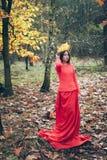 Muchacha hermosa joven en vestido rojo con la corona del amarillo le del otoño Imagen de archivo