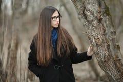 Muchacha hermosa joven en vidrios azules de una bufanda de la capa negra que camina en el otoño/la primavera Forest Park Una much Imágenes de archivo libres de regalías