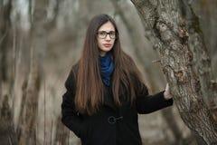 Muchacha hermosa joven en vidrios azules de una bufanda de la capa negra que camina en el otoño/la primavera Forest Park Una much Fotografía de archivo
