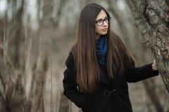 Muchacha hermosa joven en vidrios azules de una bufanda de la capa negra que camina en el otoño/la primavera Forest Park Una much Imagen de archivo