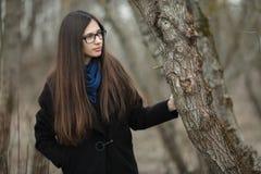 Muchacha hermosa joven en vidrios azules de una bufanda de la capa negra que camina en el otoño/la primavera Forest Park Una much Imagen de archivo libre de regalías