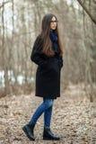Muchacha hermosa joven en vidrios azules de una bufanda de la capa negra que camina en el otoño/la primavera Forest Park Una much Imagenes de archivo