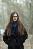 Muchacha hermosa joven en vidrios azules de una bufanda de la capa negra que explora el otoño/la primavera Forest Park Una muchac Imagen de archivo libre de regalías