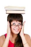 Muchacha hermosa joven en vidrios con los libros en la cabeza. aislado encendido Imágenes de archivo libres de regalías