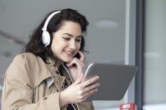 Muchacha hermosa joven, estudiante, escuchando la música y mirando Imagen de archivo libre de regalías