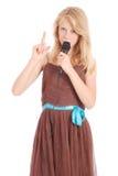 Muchacha hermosa joven feliz que canta con el micrófono Foto de archivo