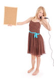 Muchacha hermosa joven feliz que canta con el micrófono Foto de archivo libre de regalías