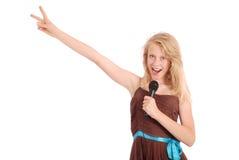 Muchacha hermosa joven feliz que canta con el micrófono Fotos de archivo