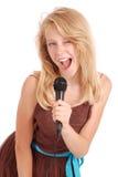 Muchacha hermosa joven feliz que canta con el micrófono Imagenes de archivo