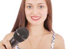 Muchacha hermosa joven feliz que canta con el micrófono Imagen de archivo