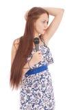 Muchacha hermosa joven feliz que canta con el micrófono Imágenes de archivo libres de regalías