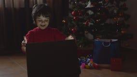 Muchacha hermosa joven que abre el regalo de Navidad - 4k metrajes