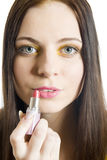 Muchacha hermosa joven que aplica el lápiz labial en sus labios Foto de archivo
