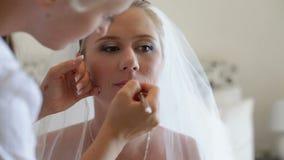 Muchacha hermosa joven que aplica maquillaje metrajes