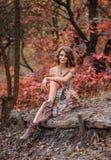 Muchacha hermosa joven que camina en bosque del otoño Fotos de archivo libres de regalías