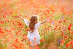 Muchacha hermosa joven que camina y que baila a través de un campo de la amapola, Fotografía de archivo libre de regalías