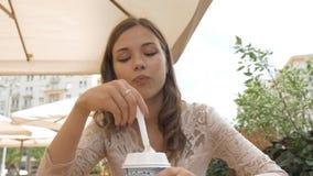 Muchacha hermosa joven que come el helado en un café de la calle Ella es feliz almacen de video