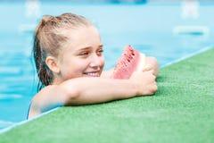 Muchacha hermosa joven que come la sandía en piscina Imagen de archivo
