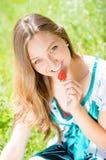 Muchacha hermosa joven que come las fresas al aire libre Fotografía de archivo