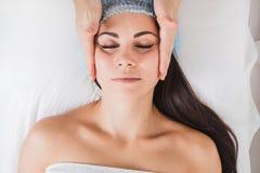 Muchacha hermosa joven que consigue un masaje facial en un salón de belleza fotografía de archivo
