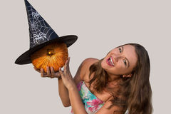Muchacha hermosa joven que detiene la calabaza y a la bruja negra h de Halloween Imágenes de archivo libres de regalías
