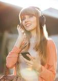 Muchacha hermosa joven que escucha el reproductor Mp3 Imágenes de archivo libres de regalías