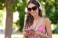 Muchacha hermosa joven que escucha la música con la tableta digital Foto de archivo