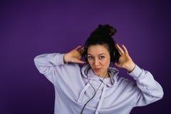 Muchacha hermosa joven que escucha los auriculares que llevan de la música en una camiseta en un fondo púrpura Fotografía de archivo libre de regalías