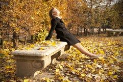 Muchacha hermosa joven que goza del sol caliente del otoño Foto de archivo