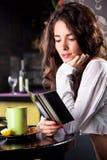Muchacha hermosa joven que goza en barra del café Imágenes de archivo libres de regalías