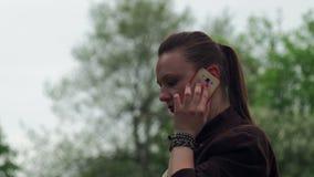 Muchacha hermosa joven que habla en el teléfono en el parque de la ciudad, al aire libre almacen de video