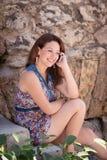 Muchacha hermosa joven que habla en un teléfono celular Imagen de archivo libre de regalías