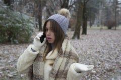 Muchacha hermosa joven que habla en un teléfono móvil Imágenes de archivo libres de regalías