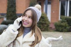 Muchacha hermosa joven que habla en un teléfono móvil Foto de archivo libre de regalías