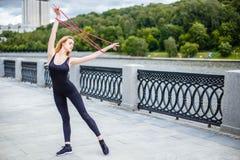Muchacha hermosa joven que hace ejercicios gimnásticos al aire libre Imagen de archivo libre de regalías