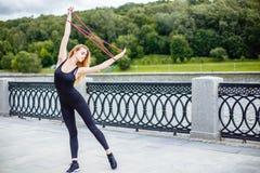 Muchacha hermosa joven que hace ejercicios gimnásticos al aire libre Fotografía de archivo