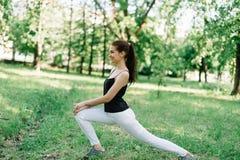 Muchacha hermosa joven que hace yoga al aire libre en el parque imágenes de archivo libres de regalías