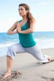 Muchacha hermosa joven que hace yoga en la playa imagen de archivo libre de regalías