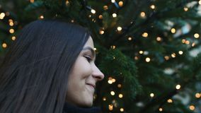 Muchacha hermosa joven que inhala el olor del árbol de navidad, humor festivo, primer almacen de metraje de vídeo