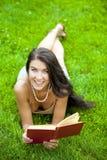 Muchacha hermosa joven que lee un libro al aire libre Imagen de archivo