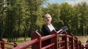 Muchacha hermosa joven que lee un libro en un parque verde en el puente Pelo rubio almacen de metraje de vídeo