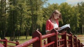 Muchacha hermosa joven que lee un libro en un parque verde en el puente Pelo rubio en el viento almacen de metraje de vídeo