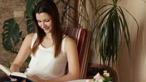 Muchacha hermosa joven que lee un libro que se sienta en una silla Mujer atractiva que sonríe mientras que lee un libro Emociones almacen de metraje de vídeo