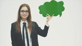 Muchacha hermosa joven que lleva a cabo una burbuja verde para el texto, aislada en un fondo blanco metrajes