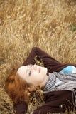 Muchacha hermosa joven que miente en el campo amarillo del otoño. Fotos de archivo libres de regalías
