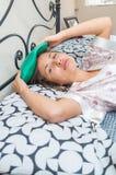 Muchacha hermosa joven que miente en la cama que siente enferma Fotografía de archivo