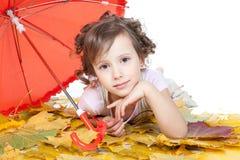 Muchacha hermosa joven que miente en las hojas de otoño imagenes de archivo
