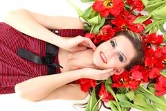Muchacha hermosa joven que miente en los tulipanes Imagen de archivo