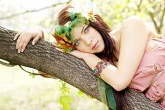 Muchacha hermosa joven que miente en un tronco de árbol imágenes de archivo libres de regalías