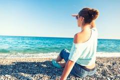 Muchacha hermosa joven que mira hacia horizonte del océano en beac del guijarro Fotografía de archivo